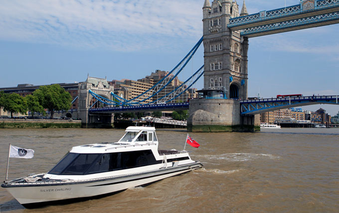 Prestigious Woods' Silver Fleet motor boat passing underneath the Tower of London