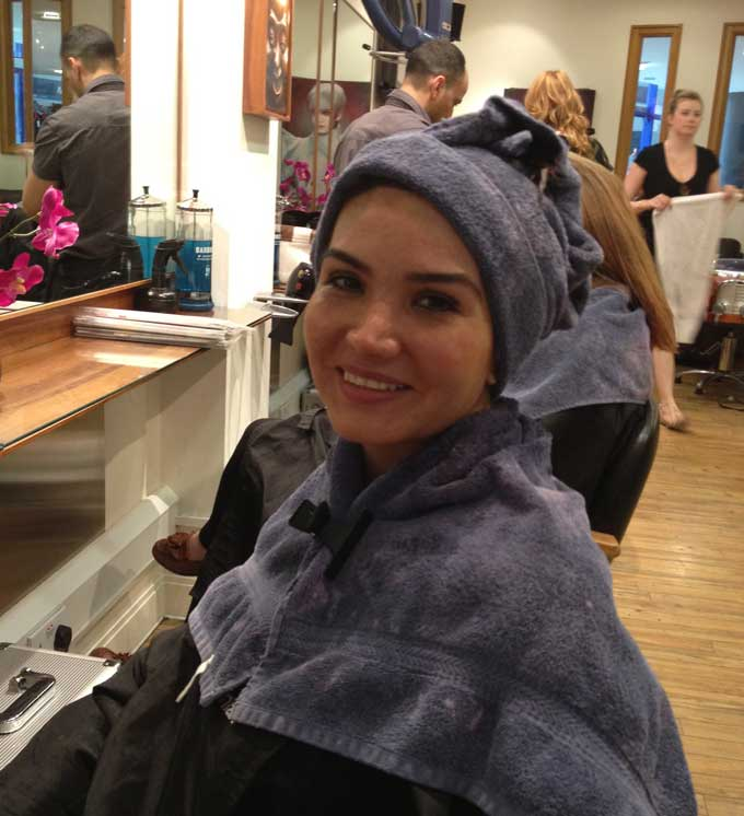 Towel on head at hair salon waiting for colour to set in