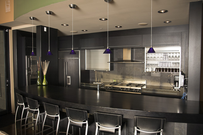 Large luxurious kitchen finished in matt black with granite and marble