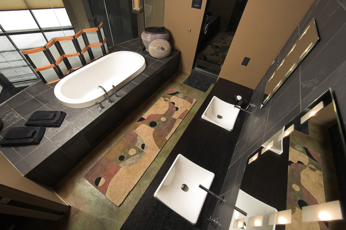 interior wide angle view looking down on large luxury bathroom with double sinks and jacuzzi hot-tub