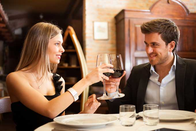 a couple clinking wine glasses on their first date at a restaurant